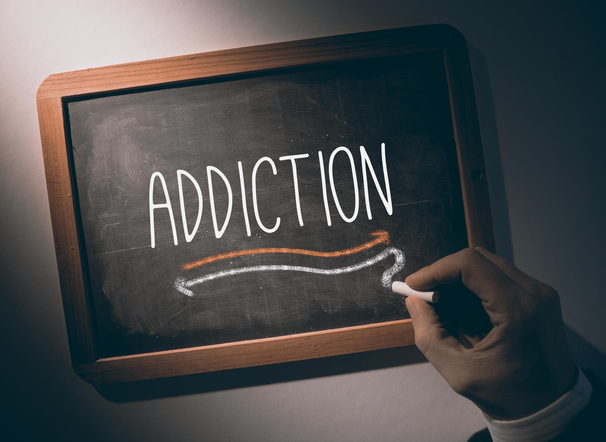 Hand writing the word addiction on black chalkboard